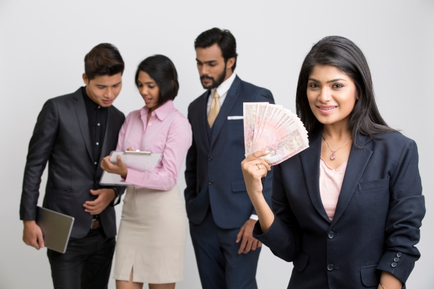 Indian businesswoman holding rupees with her busy colleagues